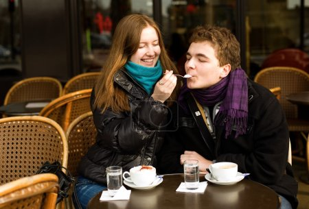 Happy couple in a Parisian street cafe