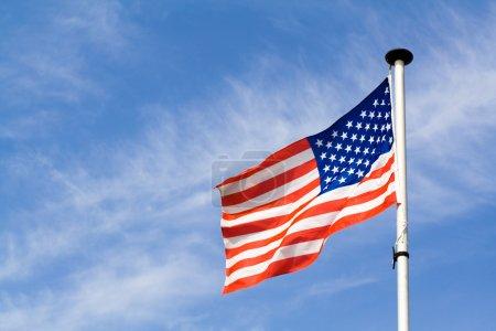 Photo pour Agitant le drapeau américain sur fond de ciel bleu - image libre de droit