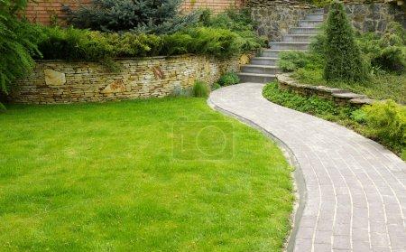 Photo pour Chemin de Pierre jardin avec gazon grandissant entre les pierres - image libre de droit