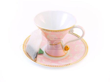Pink tea cup on a saucer and a tea bag
