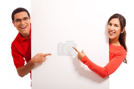 Happy couple pointing to copy space