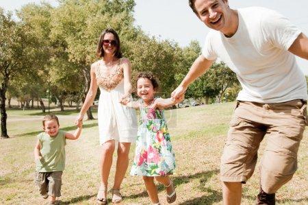 Photo pour Jeune famille jouer et courir avec deux jeunes enfants, se concentrer sur le père - image libre de droit