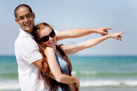 Couple smiling and pointing at the sea