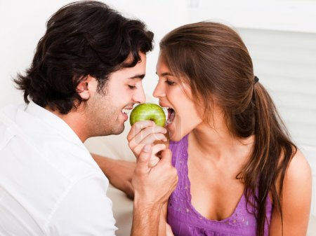 Young couple biting green apple