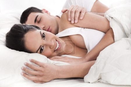 Loving husband and wife lying in bed