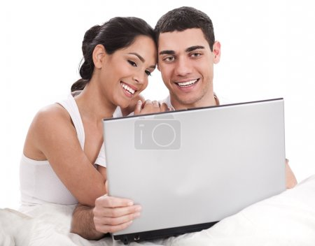 Couple sitting in bed with laptop