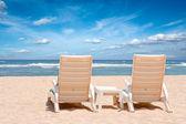 Two chaise longues on beach near ocean