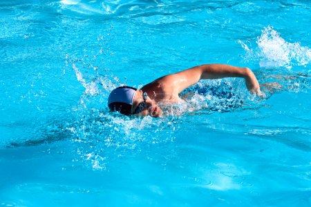 Photo pour Homme athlétique nageant dans la piscine - image libre de droit