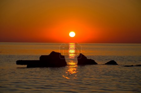 Photo for Beautiful dawn with a gold reflexion on ripples of the sea and stones - Royalty Free Image