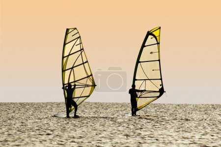 Silhouettes of two windsurfers on waves