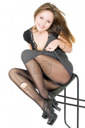 Smiling girl in the torn stockings sits