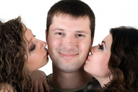 Two beautiful girls kiss the young man