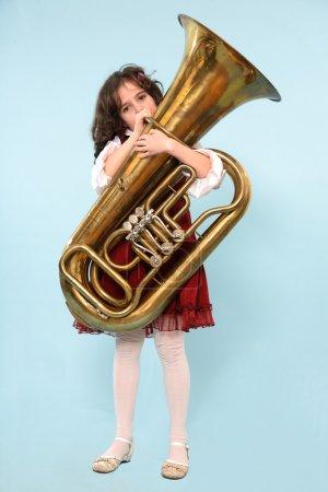 Photo pour Une fille jouant tuba isolé sur fond bleu clair. - image libre de droit