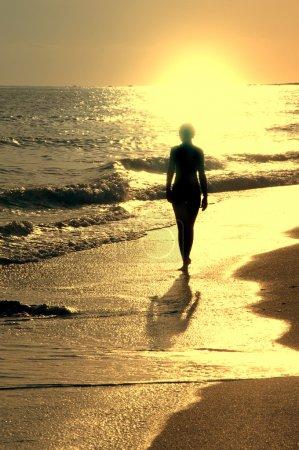 Photo pour Coucher de soleil sur la mer et fille seule sur la plage - image libre de droit