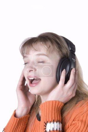 Photo pour Jeune fille écoutant de la musique et le chant sur fond blanc - image libre de droit