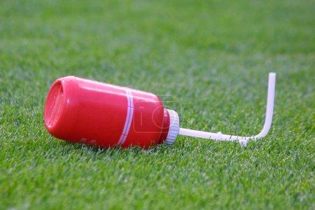 Photo pour Gros plan bouteille d'eau sportive en plastique sur l'herbe - image libre de droit