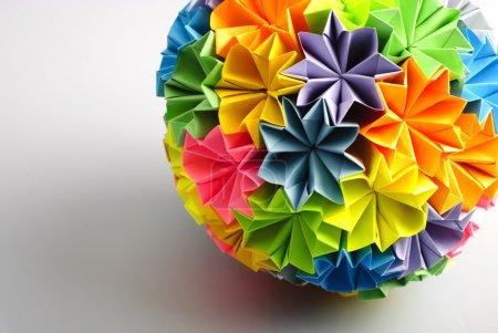 Foto de Colorfull origami kusudama de arco iris flores aisladas sobre fondo blanco. Close-up con sombra. - Imagen libre de derechos