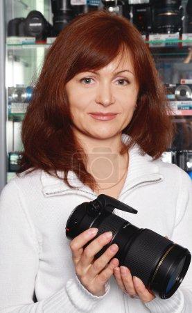 Foto de Mujer - el vendedor en una tienda fotográfica anuncia la lente - Imagen libre de derechos