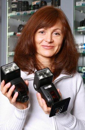 Foto de El vendedor de mujer de la fototécnica representa las linternas en un fondo de escaparates de la tienda - Imagen libre de derechos