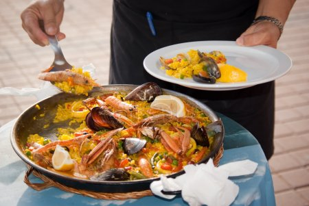 Photo for Hands of a waiter putting a portion of spanish paella on a plate - Royalty Free Image