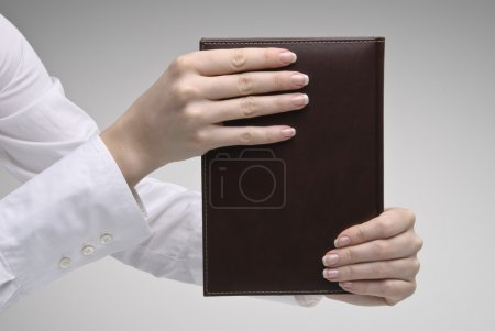 Woman's hand holding brown diary