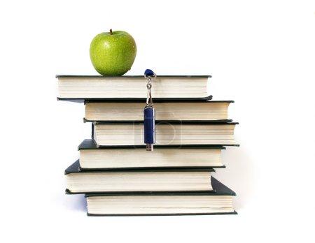 Foto de Pila de libros, memoria flash y apple aislado en blanco - Imagen libre de derechos