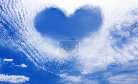 Photo pour Nuages blancs faisant une forme de coeur contre un ciel bleu - image libre de droit