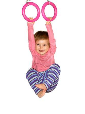 Cute girl hangs from rings