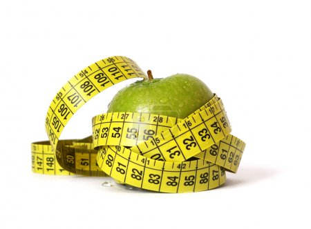 Photo for Green apple and tape measure isolared on white - Royalty Free Image
