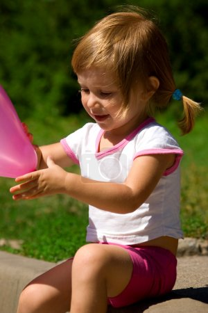 Little girl with a pink balloon
