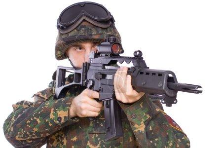 Photo pour Un soldat avec le pistolet dans les mains sur un fond blanc - image libre de droit