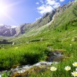 Mountain landscape with the small river, sun and c...