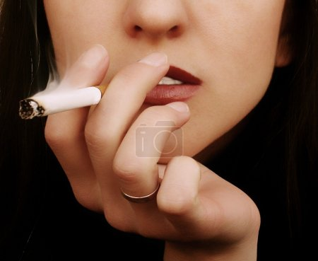 Photo for Color photo with the smoking young dark-haired woman - Royalty Free Image