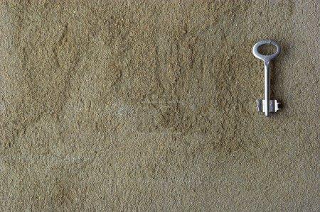 Iron key on a concrete wall