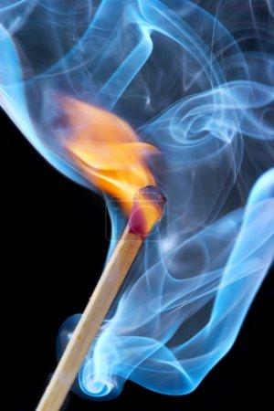 Foto de Foto de un fósforo ardiente en un humo sobre un fondo negro - Imagen libre de derechos