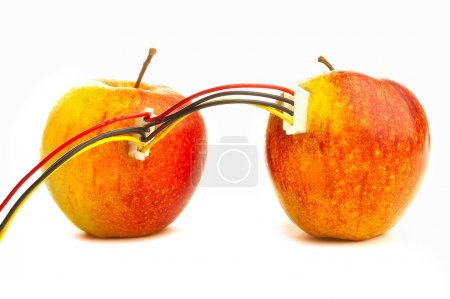 Two fresh apples connected by wires.