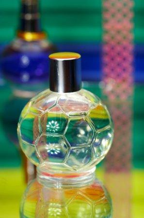 Photo pour Bouteilles en verre avec la parfumerie. sur un fond de couleur avec reflet... - image libre de droit