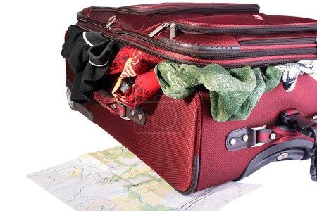 Photo pour Une grosse valise rouge avec des trucs qui sortent. Une valise en cours d'emballage. Sous une valise se trouve la carte de voyage développée . - image libre de droit