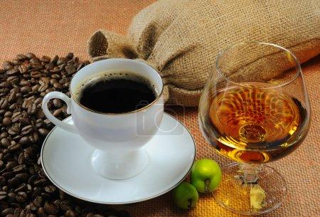 Photo pour Tasse de café, verre de cognac et sacs de grains de café - image libre de droit