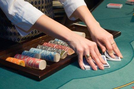 Photo pour Concessionnaire manutention et passant par les cartes à jouer à une table de poker au casino - image libre de droit