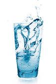 Stříkající vodě ve sklenici. sklo je isolat