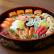 Sushi and rolls on the tray on the table.