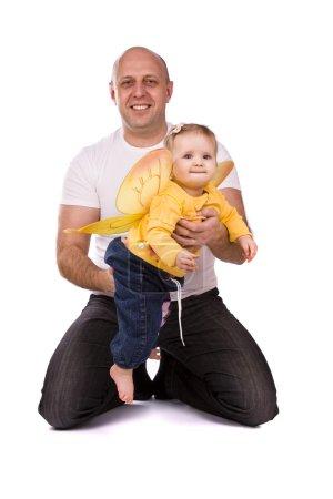 Photo pour Bonne famille. Père et petite fille sont assis par terre. L'homme et le bébé s'étreignent sur fond blanc. Les hommes tiennent petite abeille . - image libre de droit
