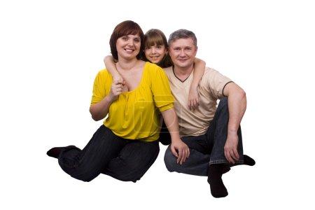 Photo pour Bonne famille. Mère, père et petite fille sourient. Femme, homme et fille sont couchés sur le sol et posant joyeusement sur fond blanc . - image libre de droit