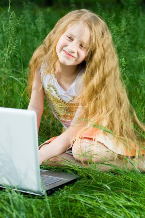 Funny little girl sitting with laptop ou