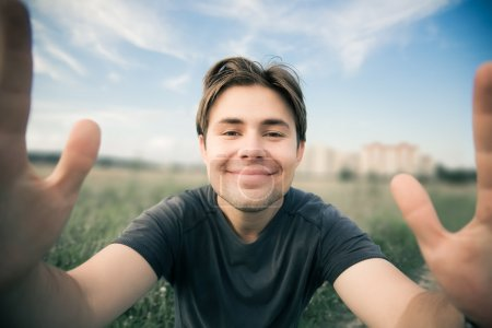 Young happy man stretching to the camera