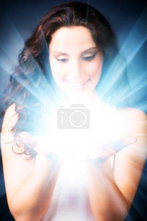 Foto de Mujer joven con brillo mágico en las manos. sobre fondo oscuro. - Imagen libre de derechos