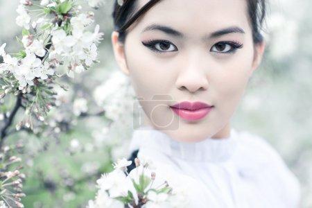 Photo pour Jeune femme avec des fleurs de cerisier. effet de faible profondeur DDL. - image libre de droit