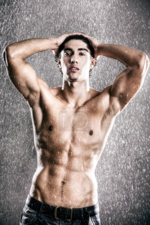 Young muscular man under the rain