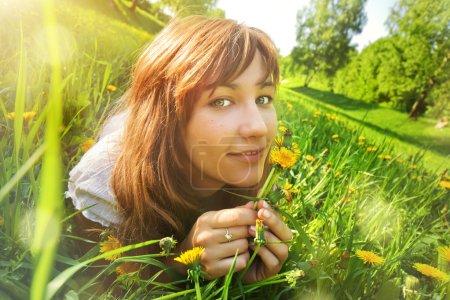 Photo pour Jeune femme allongée sur l'herbe avec des fleurs. Vue grand angle . - image libre de droit